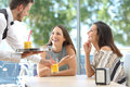 Friends Meeting In A Bar With A Waiter Serving Royalty Free Stock Image - 80697946