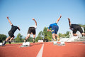 Close-up Side View Of Cropped People Ready To Race On Track Field Royalty Free Stock Photography - 80825737