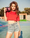 Young Sexy Smiling Photographer Woman, Holding And Making Picture On Pink Retro Vintage Camera, Wearing Red Top And Jeans Shorets, Royalty Free Stock Image - 80911076
