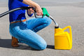 Woman Filling Yellow Can With Gasoline Or Petrol Royalty Free Stock Photo - 80941475