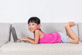 Smiling Asian Chinese Little Girl Laying On Sofa Using Laptop Royalty Free Stock Images - 80945669