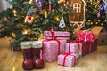 Gifts In Red And White Packaging Under The Green Christmas Tree Decorated With Christmas Toys And Candles Royalty Free Stock Photos - 80950268
