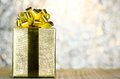 Gold Christmas Gift Box With Ribbon And Bow On Bokeh Lights Back Royalty Free Stock Photos - 81011068