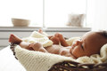 Adorable Baby Lying In Wicker Cradle By Window Stock Photos - 81070993