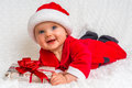 Funny Santa Baby Girl Lying On White Blanket With Gift Stock Image - 81071131