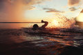 Athletic Man Is Trained To Swim In A Lake At Sunset. It Flies A Lot Of Water Splashing Stock Photography - 81176182