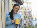 Latin Woman Drinking Cup Of Coffee Or Tea Smiling Happy At Apartment Window Balcony Stock Image - 81233601