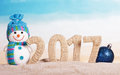 Inscription 2017 In The Sand, Snowman, Christmas Ball Royalty Free Stock Images - 81324229
