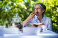 Senior Woman Eating Sweet Food In Garden Stock Photo - 81440640