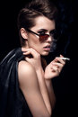 Fashion Model Smoking Cigarette Wearing Sunglasses. Sexy Woman Portrait Over Dark Background. Attractive Fashion Girl Posing. Royalty Free Stock Images - 81765709