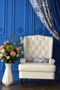 White Chair A Vase Of Flowers In The Room With Blue Walls Royalty Free Stock Photos - 81780028