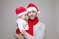 Father With Baby Boy Wearing Santa Hats Celebrating Christmas Stock Images - 81835404