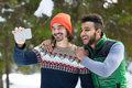 Two Man Hold Smart Phone Camera Taking Selfie Photo Snow Forest Mix Race Couple Outdoor Winter Royalty Free Stock Photo - 81871875