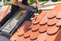 Hands Of Roofer Laying Tile On The Roof. Installing Natural Red Tile Using Hammer. Stock Photography - 81934322