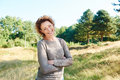 Happy Woman Standing With Arms Crossed In Park Royalty Free Stock Photo - 81976925