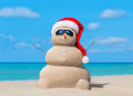 Snowman In Christmas Santa Hat And Sunglasses At Ocean Beach Stock Photo - 82033660