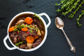 Beef Bourguignon In A White Soup Bowl On Black Stone Background, Top View. Stew With Carrots, Onions, Mushrooms, Bacon Royalty Free Stock Photography - 82138127