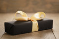 Handmade Gift Black Paper Box With Yellow Ribbon Bow On Wood Table Stock Photography - 82183932