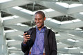 Smiling Black Businessman Smiling And Looking At Mobile Phone Royalty Free Stock Photos - 82233068