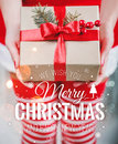 Female Hands Holding Christmas Gift Box With Red Ribbon And Merry Christmas And New Year Typographical On Shiny Xmas Background Stock Photos - 82252963