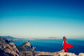 Young Beautiful Woman In Red Dress Looking To Mountains Sea Royalty Free Stock Image - 82508776