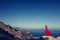Young Beautiful Woman In Red Dress Looking To Mountains Sea Stock Photo - 82508780