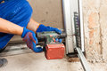 Garage Doors Installation. Worker Use Automatic Screwdriver  To Fix A Bolt. Stock Photo - 82528480