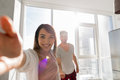 Young Couple Taking Selfie Photo Holding Hands In Kitchen, Asian Woman Leading Hispanic Man Stock Image - 82654261