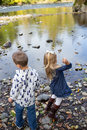 Siblings Throwing Rocks In River Together Stock Image - 82673261