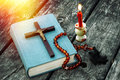 Closeup Of Wooden Christian Cross On Bible, Burning Candle And Prayer Beads On The Old Table. Stock Image - 82719241