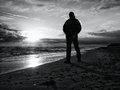 Man At Evening Sea. Hiker With Backpack With Hands In Pocket Along Beach. Royalty Free Stock Photo - 82751025