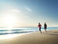 Man And Women Running On Tropical Beach At Sunset Stock Images - 82882824