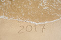 New Year 2017 Is Coming Concept - Inscription 2016 And 2017 On A Beach Sand, The Wave Is Almost Covering The Digits 2016 Stock Image - 82940501