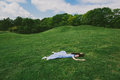 Brunette Woman Lying On Her Stomach On The Green Grass Stock Photography - 82944862