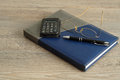 A Calculator, Pen And Reading Glasses On Top Of A Note Book Stock Image - 82999171