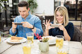 Cute Couple Taking Pictures Of Their Food Royalty Free Stock Photo - 83014325