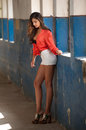 Beautiful Girl With Red Shirt And White Shorts Posing In Old Hall With Columns Blue Painted. Attractive Long Hair Brunette Stock Photos - 83160913