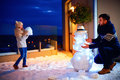 Happy Father And Son Making Snowman In Evening Light Royalty Free Stock Photo - 83351605