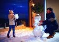 Happy Father And Son Making Snowman In Evening Light Stock Image - 83351611