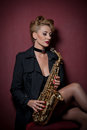 Sexy Attractive Woman With Saxophone Posing On Red Background. Young Sensual Blonde Playing Sax. Musical Instrument, Jazz Stock Images - 83383314