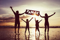Happy Family Jumping On The Beach At The Sunset Time. Stock Photography - 83642552