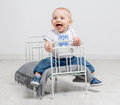 Cute Curious Baby Sitting On A Little Bed Royalty Free Stock Photography - 83668647