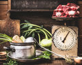 Kitchen Table With Cooking Pot, Ladle, Vegetables And Old Weigher With Raw Meat , Preparation Of Soup , Broth Or Stew, Front View Stock Image - 83699811
