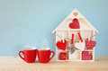 Wooden House With Many Hearts Next To Coffee Cups Stock Photos - 83702073