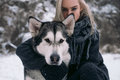 Portrait Of Girl With  Big Malamute Dog On Winter Background. Stock Photos - 83762603