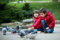 Two Cute Children, Boy Brothers, Feeding Pigeons In The Park Royalty Free Stock Photos - 83802028