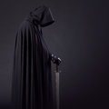 Portrait Of A Courageous Warrior Wanderer In A Black Cloak And Sword In Hand. Royalty Free Stock Photos - 83865408