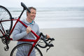 Man Carrying Bicycle On Beach Stock Photography - 84087282
