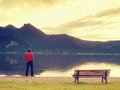 Tall Man In Red T-shirt At Wooden Bench At Mountains Lake Coast. Dark Clouds Stock Image - 84150371