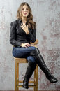 Young Girl With Curly Hair In A Black Shirt, Jeans And High Boots Cowboy Western Style Royalty Free Stock Photo - 84189815